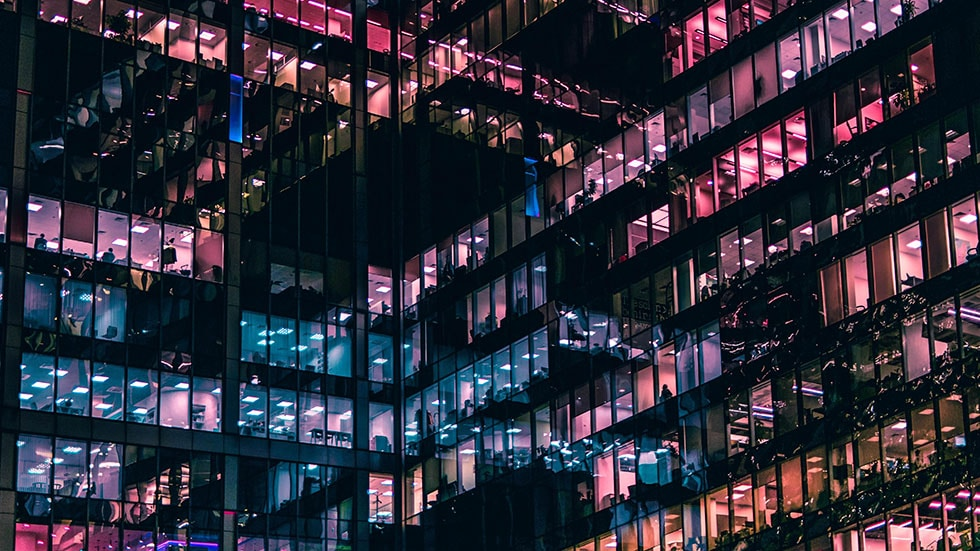 Apartment building with pink and blue lights from windows